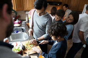 Latinx multi-generation family cooking, cutting avocados in kitchen