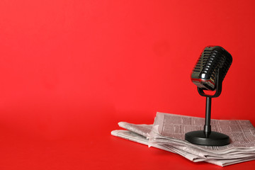 Newspapers and vintage microphone on red background, space for text. Journalist's work