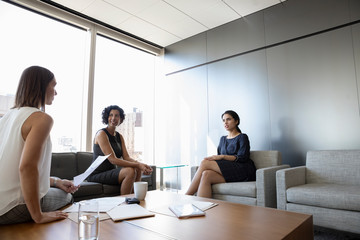 Businesswomen discussing paperwork in office lounge meeting