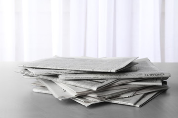 Pile of newspapers on grey table. Journalist's work