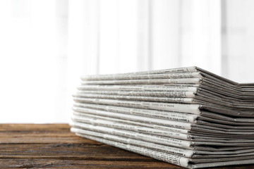 Stack of newspapers on wooden table. Journalist's work