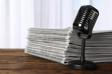 Newspapers and vintage microphone on wooden table. Journalist's work