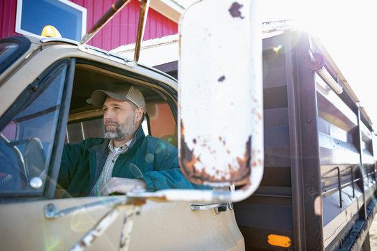 Male farmer driving trailer truck