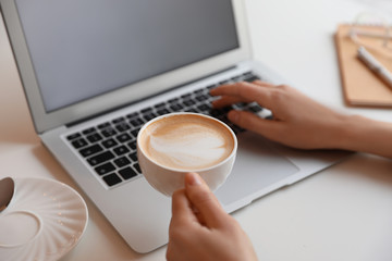 Young blogger with cup of coffee working at table in cafe, closeup Wall mural