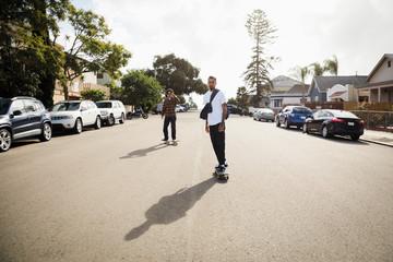 Latinx young men skateboarding on sunny neighborhood street