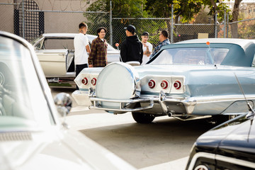 Latinx men friends hanging out in parking lot with low rider vintage cars