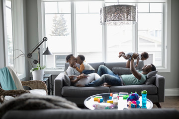 Affectionate young family on living room sofa