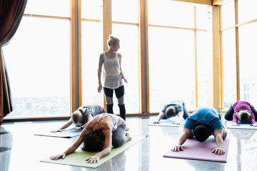 Female instructor leading yoga class practicing childs pose in studio