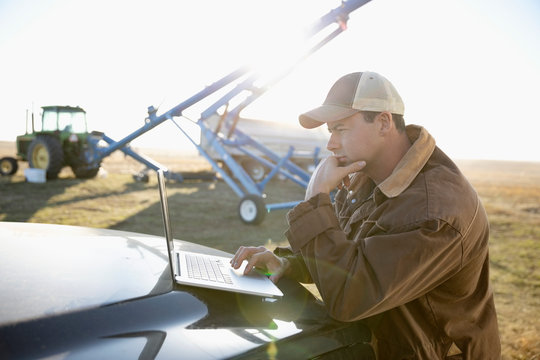Male farmer using laptop on truck on sunny farm