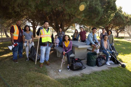 Portrait confident volunteers cleaning park