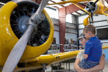 Female army pilot mother showing son airplane in military airplane museum Fototapete