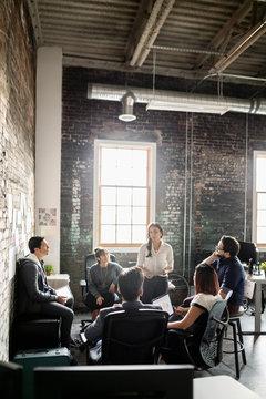 Creative businesswoman leading meeting in loft office