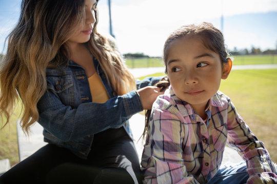 Latinx girl braiding sister s hair