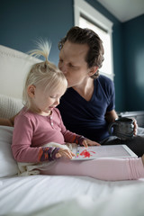 Affectionate father kissing toddler daughter using digital tablet on bed