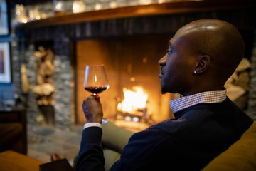 Man drinking red wine by fireplace in hotel lobby