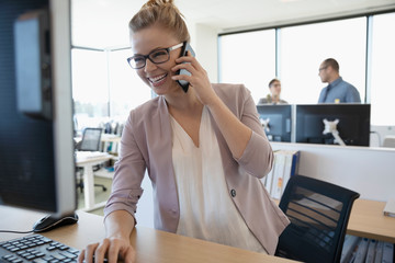 Laughing businesswoman talking on cell phone at computer in office