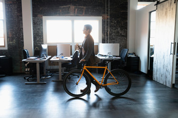 Creative businessman walking bicycle in loft office