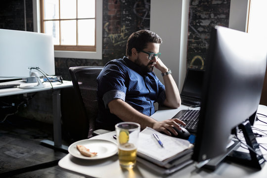 Creative businessman working and eating pizza and drinking beer at desk