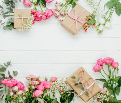 Craft paper wrapping gift boxes and flowers on white wooden background
