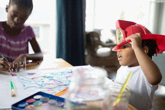 Cute toddler boy wearing fireman s helmet and painting at dining table