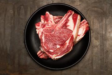 Chuletón de carne cruda de vaca sobre plato negro redondo. Vista superior