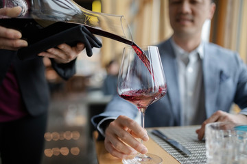 Sommelier pouring red wine for man dining in restaurant