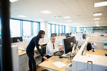 Business people working at computer in office cubicle