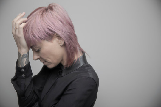 Beautiful non-binary gender person with pink hair and head in hands
