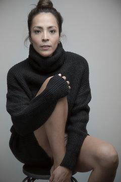 Portrait confident beautiful Latina woman wearing sweater dress