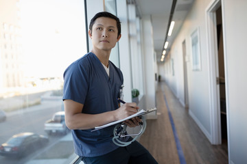 Thoughtful male nurse with clipboard in clinic corridor