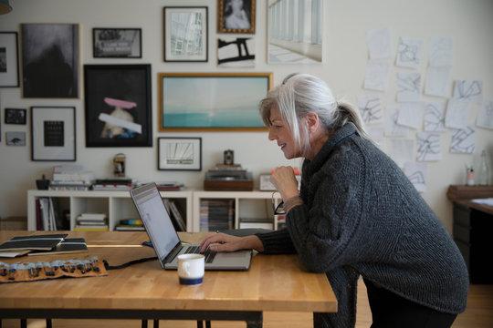 Senior woman working at laptop in studio