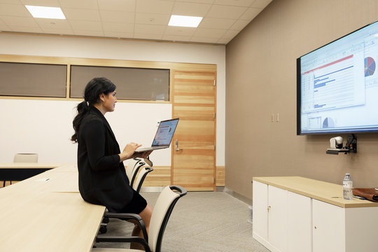 Businesswoman preparing audio visual presentation in conference room