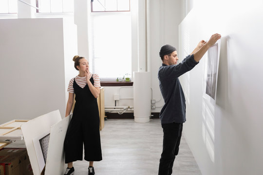 Art gallery owners hanging prints