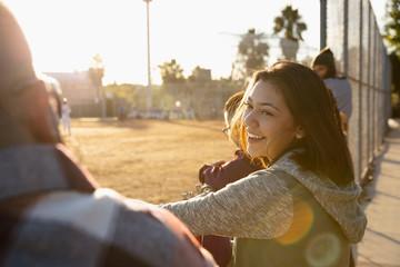 Smiling Latinx young woman watching baseball game
