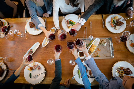 View from above business people toasting red wine glasses at restaurant table