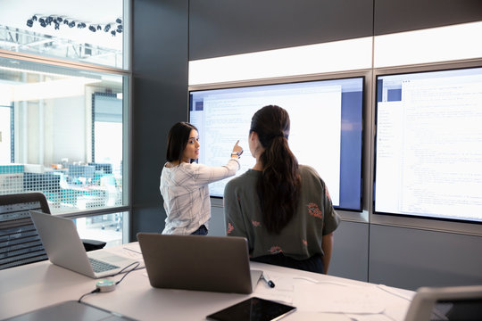 Female computer programmers reviewing code at touch screen in conference room meeting