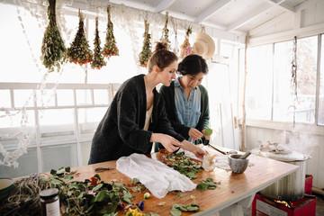Women drying flowers for paper making in studio