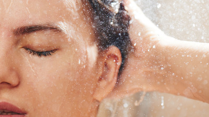 Girl in the shower under stream of water washes her hair, wet face close-up, enjoys eyes closed
