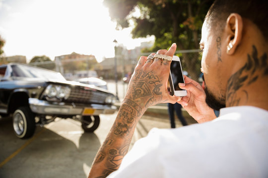 Latinx man with tattoos photographing low rider car bouncing in parking lot