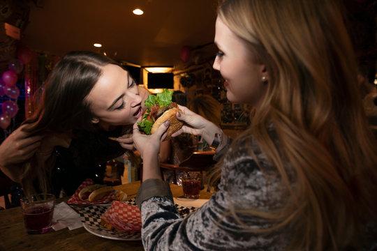 Women friends sharing hamburger at late night diner