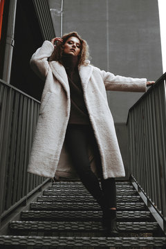 A girl with red curly hair in a white coat poses on the parking stairs. City Style - Urban