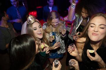Young women friends taking tequila shots in nightclub