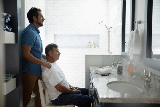 Latinx son preparing to shave senior father face in bathroom