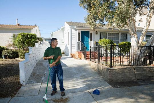 Latinx senior man sweeping driveway