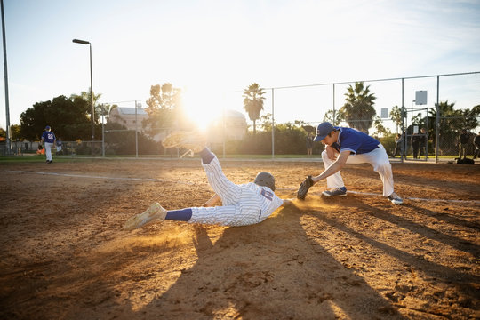 Baseball player sliding into first base on sunny field