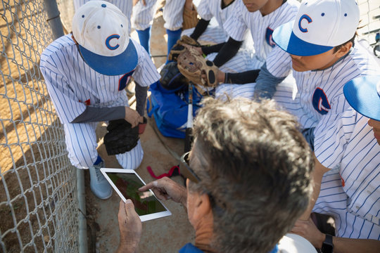 Coach with digital tablet talking to baseball team