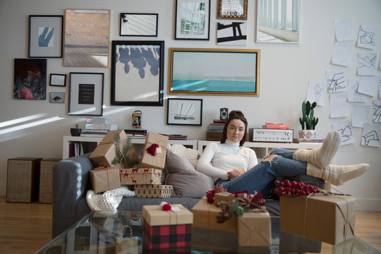 Portrait young woman surrounded by Christmas gifts in living room