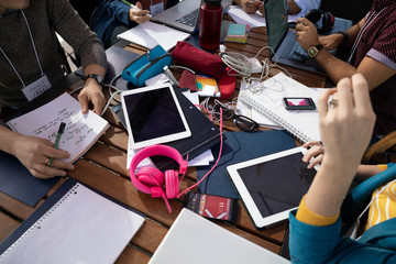 Millennial entrepreneurs working, using digital tablets and laptops at table