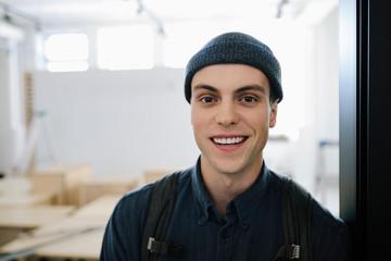 Portrait smiling male artist in art gallery