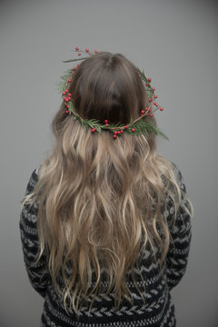 Rear view portrait young woman with long blonde hair wearing Christmas wreath in hair
